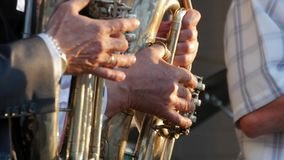 Trumpets in the hands of the musicians in the orchestra. Hands of the man playing the trumpet. Trumpets in the hands of the musicians in the orchestra. Hands of stock footage