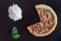 Truncated pizza, pile of flour and green leaves on black background. Directly above photo stock photos