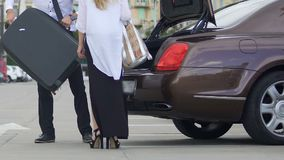 Trunk of expensive car opening, man putting females suitcase, hotel transfer. Stock footage stock video footage