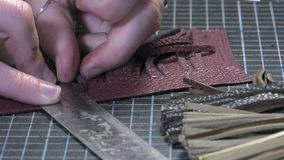 Trunk Maker at work in his workshop. Cutting leather fringes and tassels realization stock video footage