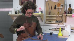 Trunk Maker at work in his workshop. Dyeing the edges of leather pieces stock video footage