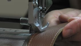 Trunk Maker at work in his workshop. Ornamental stitching the edges of leather parts stock video footage