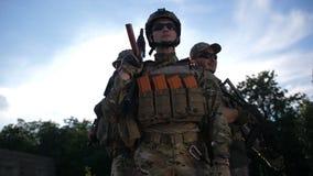 Trupp av det oavkortade kugghjulet för militära soldater på solnedgången stock video