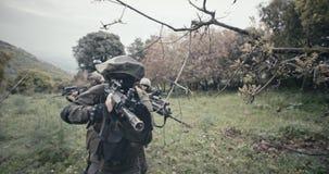 Trupp av fullst?ndigt bev?pnade kommandosoldater under strid i ett skoglandskap lager videofilmer