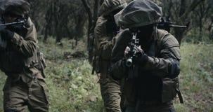 Trupp av fullst?ndigt bev?pnade kommandosoldater under strid i ett skoglandskap