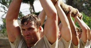 Truppe militari che portano ceppo di legno pesante durante la corsa ad ostacoli 4k archivi video