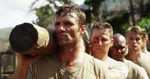 Truppe militari che portano ceppo di legno pesante durante la corsa ad ostacoli 4k stock footage