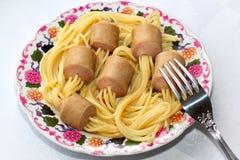 Truque do cozinheiro chefe. Espaguetes colados nas salsichas. Imagens de Stock