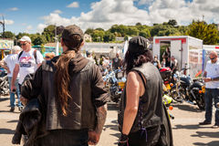 TRURO, CORNWALL, UK - JULY 17, 2016- Man and woman in black leat. Her at Lemon Quay for the Truro custom motorbike and trike motorcycle show Royalty Free Stock Image