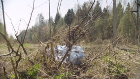 Trush bag lying in the woods. Social irresponsibility. Save the earth concept. Crane shot stock video