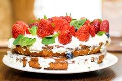 Truskawka tort w kremowych i nowych liściach na stole w talerzu obraz stock