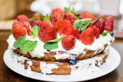 Truskawka tort w kremowych i nowych liściach na stole w talerzu fotografia stock