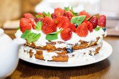 Truskawka tort w kremowych i nowych liściach na stole w talerzu zdjęcie stock