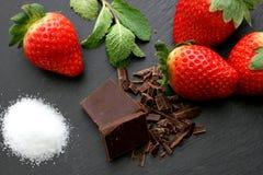 Truskawki, cytryna plasterki, nowi liście i czarna czekolada na czerni, krytykują tło Zdjęcia Stock