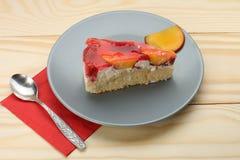 Truskawki i brzoskwini tort z gelatin na popielatym talerzu na drewnianym t Fotografia Stock