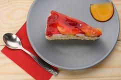 Truskawki i brzoskwini tort z gelatin na popielatym talerzu na drewnianym t Obraz Royalty Free