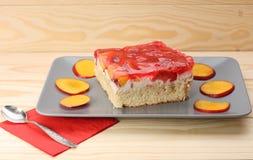 Truskawki i brzoskwini tort z gelatin na popielatym talerzu na drewnianym t Zdjęcia Royalty Free