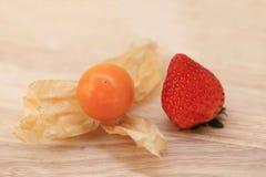 Truskawki i przylądka agresta owoc na drewnianym tle Obraz Stock