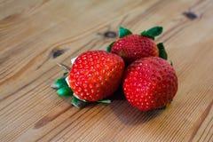 3 truskawki kłama na stole Zdjęcia Royalty Free