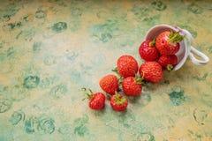 Truskawki rozlewać od filiżanki Świeże truskawki w kubku odizolowywającym na zielonym koloru żółtego stole jagody od ogródu Fotografia Royalty Free