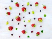 Truskawkowe i agrestowe jagody kłaść out na drewnianym białym tle Fotografia Royalty Free