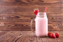 Truskawkowy potrząśnięcie w kamieniarza słoju Różowy jagodowy napój na drewnianym tle Jogurt z truskawką na wierzchołku i czerwon Obraz Stock