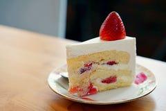 Truskawkowy shortcake nakrywający z wielką świeżą truskawką umieszczającą w bielu talerzu i na drewnianym stole z kopii przestrze Obraz Stock
