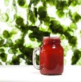 Truskawkowy smoothie lub milkshake w słoju na zieleni opuszczamy tło Zdjęcia Stock