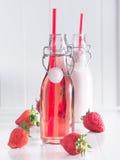 Truskawkowy soku i truskawki mleko w butelkach Fotografia Stock