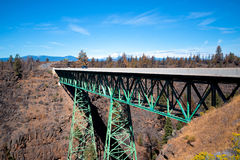 Truss metal bridge with tapered supports through deep rocky ravi. Green metal truss road bridge on two conical truss supports poles abutting the bottom of a deep Royalty Free Stock Photos