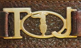 Trussardi logo. The image describes the side of a leather belt, which shows the metal logo of the famous brand Royalty Free Stock Image