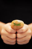 Trust. Hands holding a stone engraved with the word TRUST Stock Photography