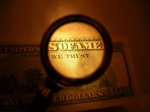 We trust. Words we trust on one hundred dollars banknote outlined by magnifying glass stock image
