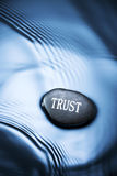 Business Trust Background. A rock with the word trust on it in with water and ripples Stock Photos