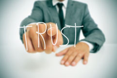 Trust. Businessman sitting in a desk pointing the word trust written in the foreground Royalty Free Stock Photography