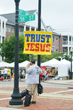 Trust Jesus. A man on the phone holding a sign that says Trust Jesus at the Kenosha, Wisconsin Harbor Farmers Market stock photography