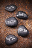 Trust Love Believe Dream Faith. Inspirational stones on a rusty metal background Royalty Free Stock Image