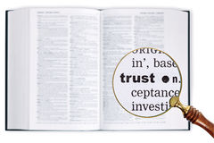 Trust through a magnifying glass over Dictionary. Stock Photo