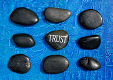 Trust stones. Engraved stone with word trust in the middle of other stones on blue textured background Royalty Free Stock Images
