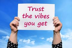 Trust the vibes you get. Motivational sign woman holding by hand royalty free stock image