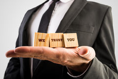 We trust you sign. Three wooden cubes aligned on a male hand with the words We trust you Stock Images