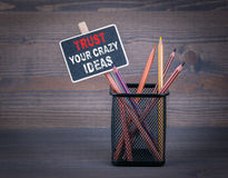 Trust Your Crazy Ideas. A small blackboard chalk and colored pencil on wood background Royalty Free Stock Photography