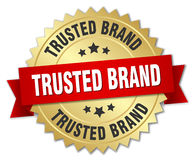 Trusted brand 3d gold badge. With red ribbon Stock Image