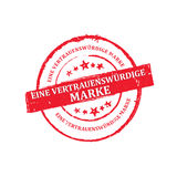 Trusted Brand Text in German language. Red grunge stamp / sticker / label for retail industry. Grunge layer is applied exactly on the colored stamp Royalty Free Stock Photography