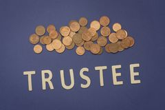 Trustee written with wooden letters on a blue background. To mean a business concept Stock Image