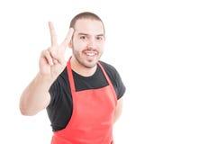 Trusthworthy hypermarket employee doing peace sign Stock Image