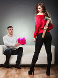 Trusting guy giving present to misleading girl Stock Images