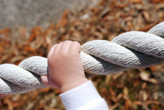 Trusting hands on a rope. A child''s hand gripping onto a rope boundary royalty free stock photography