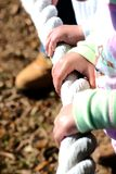 Trusting hands on a rope. A child''s hand gripping onto a rope boundary Stock Image