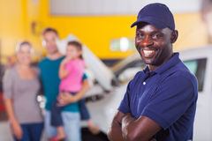 Trustworthy auto mechanic. Trustworthy african auto mechanic standing in front of family inside garage Stock Photography